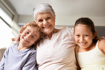 Buy stock photo A granny and her two grandkids smiling at the camera