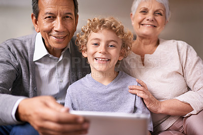 Buy stock photo A little boy holding a tablet while sitting with his grandparents