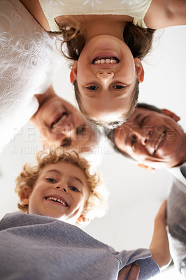 Buy stock photo Low angle shot of grandparents and their two grandchildren standing in a huddle