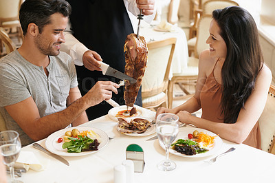 Buy stock photo A waiter cutting meat off a skewer for a young couple at their table
