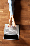 Legs of a young female relaxing on the floor with laptop