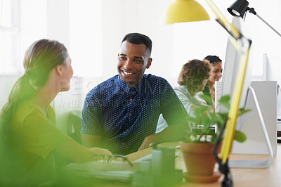 Buy stock photo Shot of a team of designers chatting while working on their computers