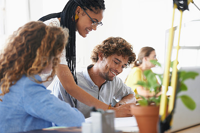 Buy stock photo Shot of a group of young coworkers working on a computer