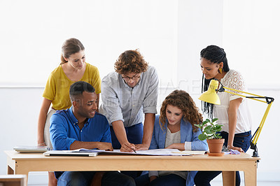Buy stock photo Shot of a group of young people meeting over documents