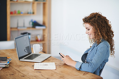 Buy stock photo Shot of a young woman using a cellphone while sitting at her desk