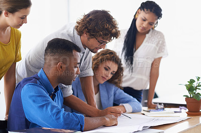Buy stock photo A group of young coworkers discussing work