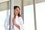 Happy woman relaxing on a glass door and looking away