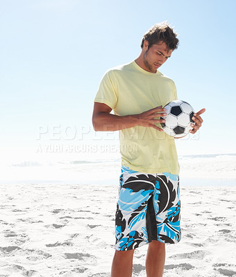 Buy stock photo A young athletic guy holding a football on the beach - copyspace