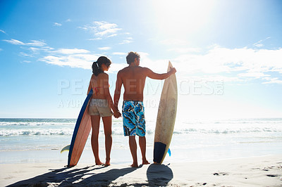 Buy stock photo Rear view image of a young couple holding surf boards by the sea shore