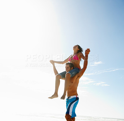 Buy stock photo Young man carrying his girlfriend on his shoulders at the beach
