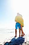 Rear view of an affectionate couple wrapped in a towel at the beach