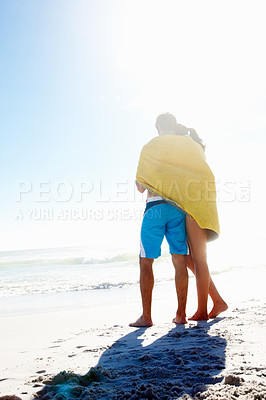 Buy stock photo Rear view a young affectionate couple wrapped in towel romancing in outdoors