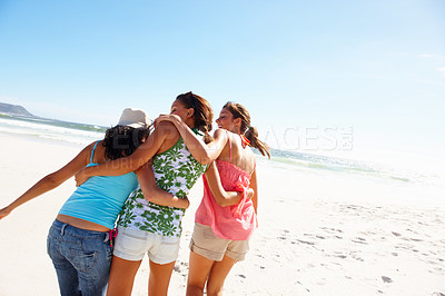 Buy stock photo Rear view of three happy teenage friends at the beach
