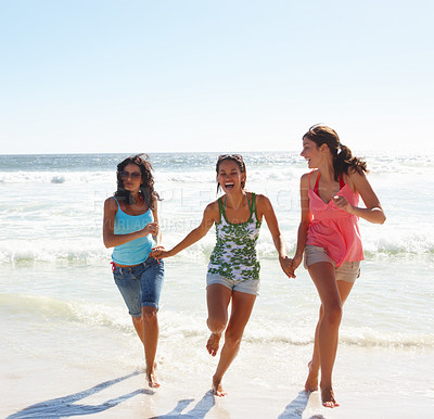 Buy stock photo Happy females running away from the sea waves