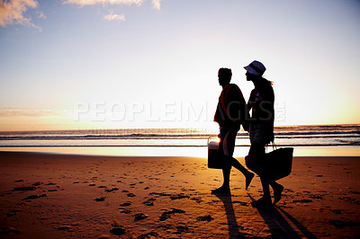 Buy stock photo Silhouette image of a couple strolling by the sea shore