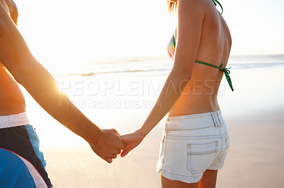 Buy stock photo Mid section image of a romantic young couple holding hands at the beach -copyspace