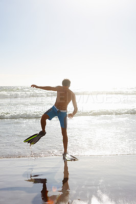 Buy stock photo A young teenage guy on the beach walking comically towards the sea wearing flippers for swimming - copyspace