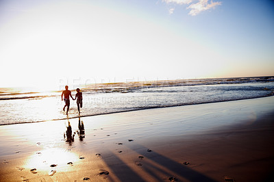 Buy stock photo Silhouette image of a couple running to the sea