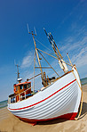 A photo of a Danish fishing boat at the beach