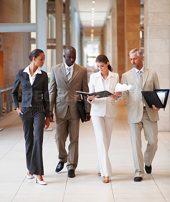 Buy stock photo Group of busy business colleagues walking through the hallway