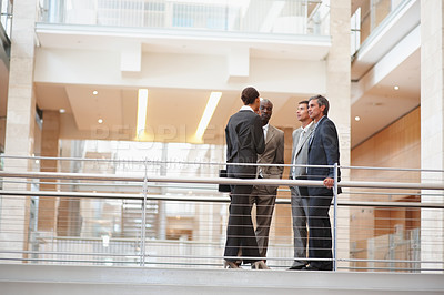 Buy stock photo Group of mixed business people discussing issues standing by a railing