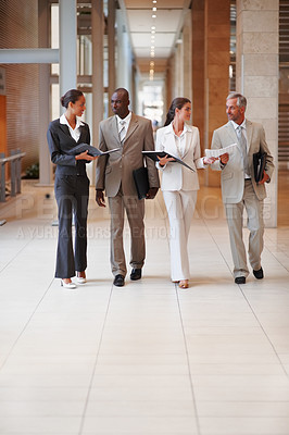 Buy stock photo Happy business colleagues holding file at a hallway
