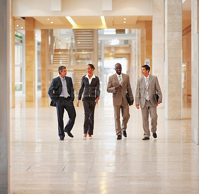 Buy stock photo Portrait of professional business people walking together in the hallway