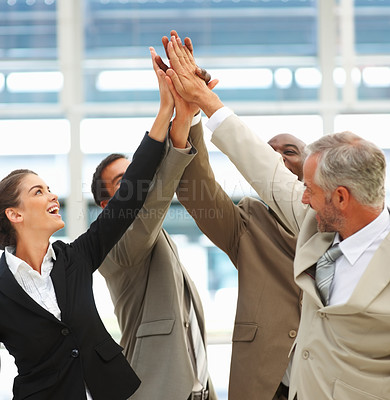 Buy stock photo Portrait of a successful business group with their hands raised together in agreement