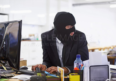 Buy stock photo Shot of a hacker dressed in a black mask hacking a computer