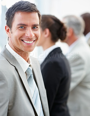 Buy stock photo Portrait of a young happy business man with his coworkers at the back
