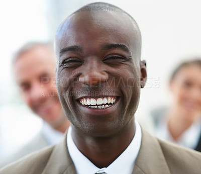 Buy stock photo Portrait of a laughing African American business man with colleagues standing behind