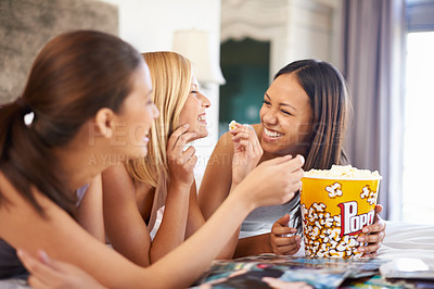 Buy stock photo Shot of three attractive young women eating popcorn on their girls' night