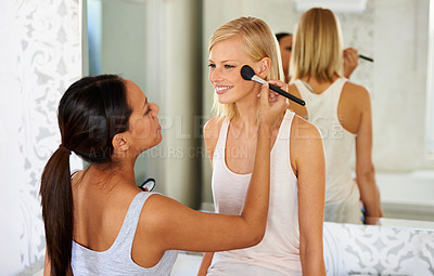 Buy stock photo Shot of a young woman doing her friend's makeup for her
