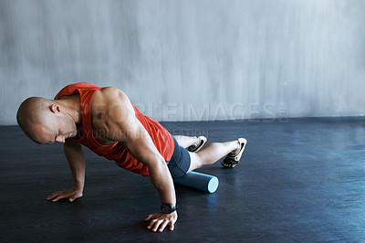 Buy stock photo A young man doing push-ups with a foam roller