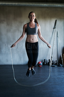 Buy stock photo Shot of a woman training with a skipping rope at the gym