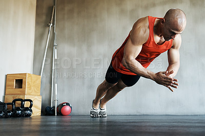 Buy stock photo Shot of a man doing exercises at the gym