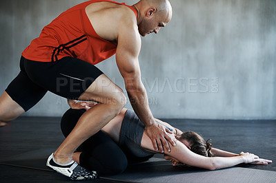 Buy stock photo Shot of a fitness trainer instructing a young woman at the gym