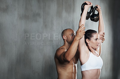 Buy stock photo A young woman exercising at the gym with a fitness instructor helping her