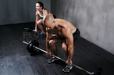Buy stock photo Shot of two people lifting barbells during a gym workout
