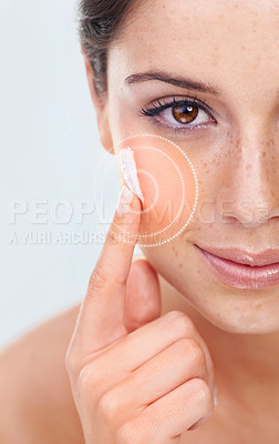Buy stock photo Studio portrait of a a beautiful young woman applying moisturizer to her cheek