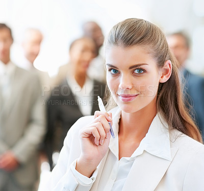 Buy stock photo Portrait of a cute young business woman with colleagues at the back