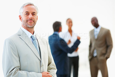 Buy stock photo A successful mature professor with staff standing at the back