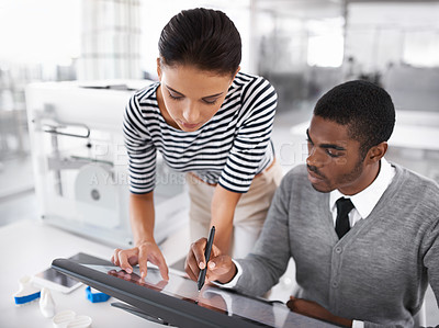 Buy stock photo Shot of two designers using a large touchscreen monitor