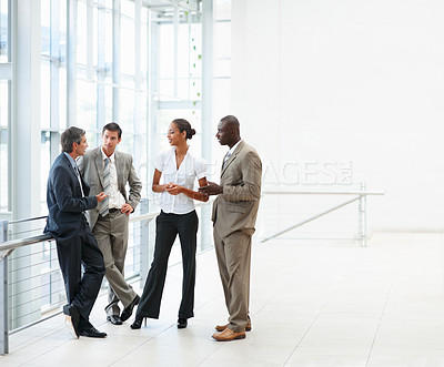 Buy stock photo Group of four business colleagues having a discussion at the hallway