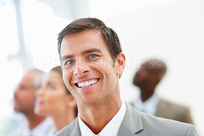 Buy stock photo A smart handsome business man smiling confidently with colleagues behind him