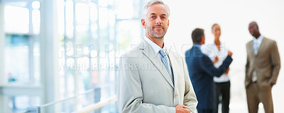 Buy stock photo Portrait of a professional mature business man with colleagues at the back