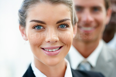 Buy stock photo Closeup image of a pretty young smiling business woman with colleagues at the back