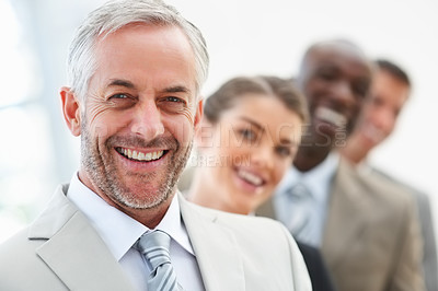 Buy stock photo Closeup portrait of a senior mature business man with his colleagues behind him