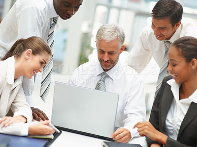 Buy stock photo A group of successful business people working together on a laptop