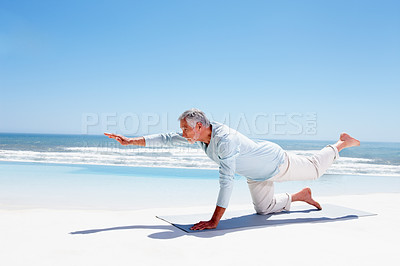 Buy stock photo Portrait of a senior man practicing yoga on the sea shore
